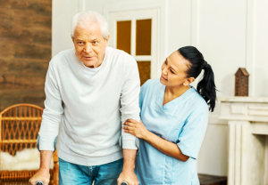 an elderly man escorted by a caregiver woman