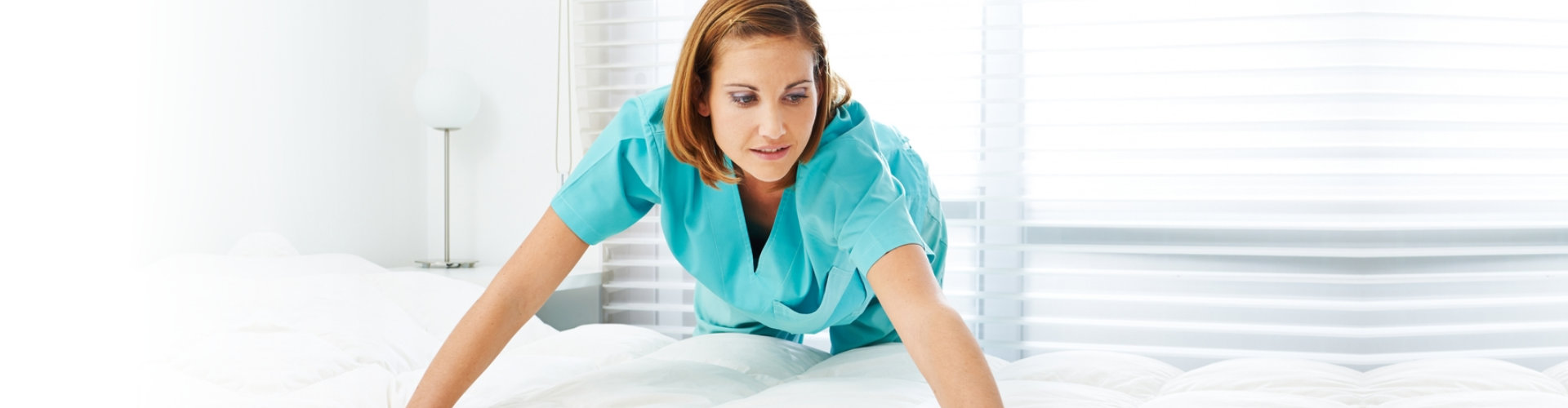 caregiver fixing the bed sheet