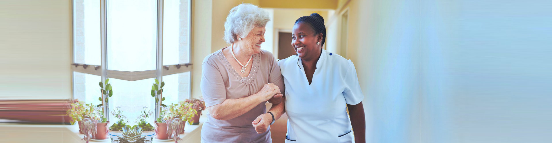 caregiver and senior woman having a conversation while walking at the hallway